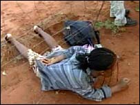A Zimbabwean woman crawls under a fence