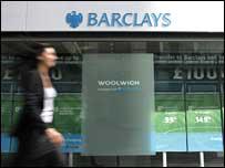 Woman walking past Barclays Bank branch