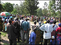 Displaced people cue for food
