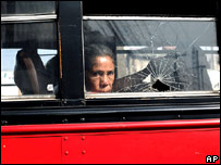 A woman looks out of a bullet-shattered bus window in Guatemala City