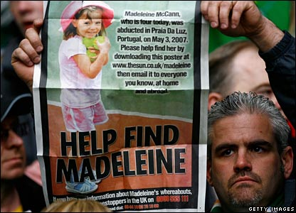 A Celtic fan holds a poster of Madeleine McCann