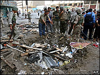 Iraqi soldiers and civilians survey the scene following a car bomb attack in Baghdad