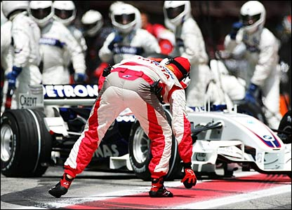 A Toyota mechanic picks up the wheel nut that has just spun off Nick Heidfeld's BMW Sauber