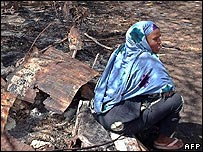 Woman sitting on ground where her home once stood