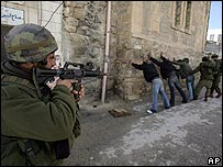 Israeli soldiers stop and search Palestinians in Hebron