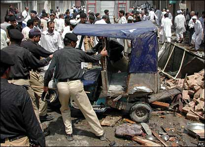 Pakistani police officers push an auto rickshaw at the site of the explosion