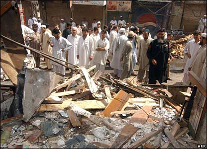 Pakistani bystanders look at the blast site at the hotel entrance