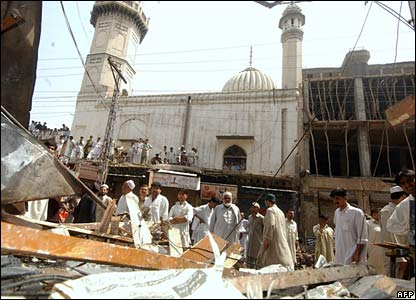 Pakistani bystanders gather at the site of a blast at the entrance to a hotel in Peshawar, 15 May