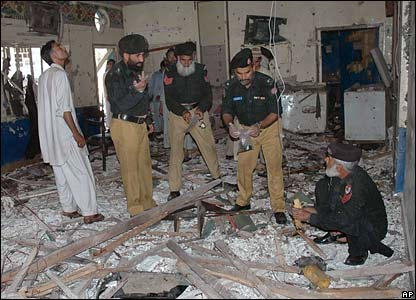Pakistani security officials examine the site of the bombing