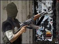 A masked Palestinian security force officer loyal to the Fatah movement takes a position in Gaza City