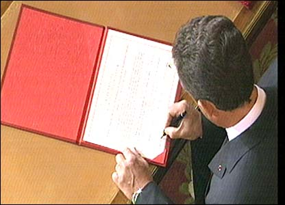 Nicolas Sarkozy signs documents at the Elysee Palace