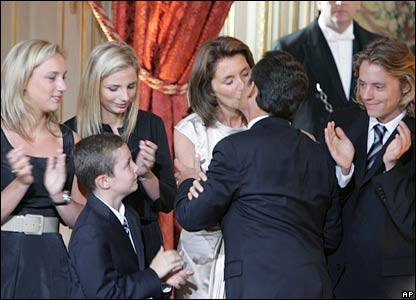 Nicolas Sarkozy kisses his wife Cecilia as their children applaud at the Elysee Palace