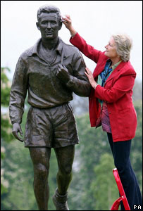 Sculptor Vivien Mallock polishes her Brian Clough statue