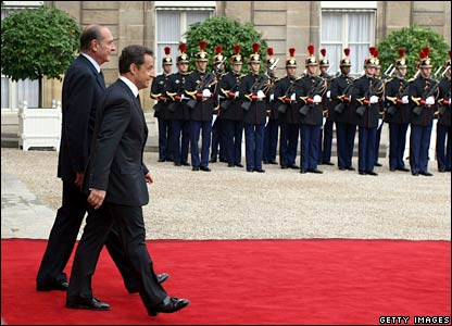 Nicolas Sarkozy escorts Jacques Chirac as the outgoing president leaves the Elysee Palace