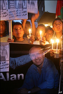 Palestinian children of hold candles and pictures of the kidnapped BBC correspondent Alan Johnston
