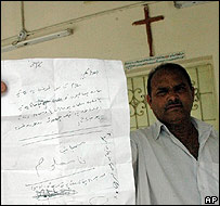 Priest Pram Samuel shows the letter ordering Christians to convert to Islam
