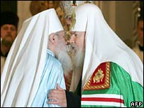 Metropolitan Lavry (left) and Russian Patriarch Alexy II kiss during the reunification ceremony