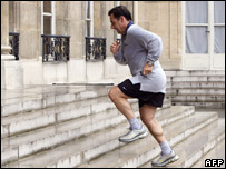Nicolas Sarkozy jogs up the steps of the Elysee Palace (after exiting from a chauffeur-driven car)