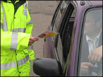 Stationary idling patrol officer handing over a leaflet