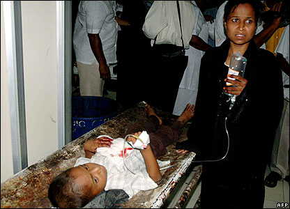Woman holds intravenous drip for wounded boy.