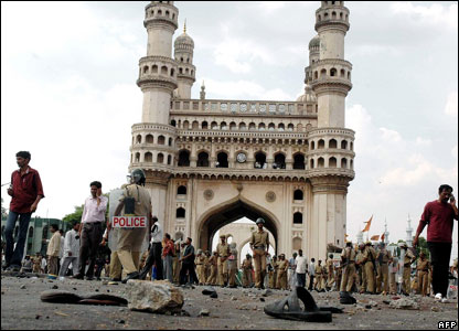 Police, journalists and others at the Char Minar gate in Hyderabad