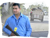 Private military contractor holding a gun, and a tank in the background