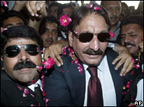 Pakistan's suspended chief justice Iftikhar Mohammed Chaudhry (R) is escorted by his supporters as he arrives at Islamabad airport to depart for Karachi