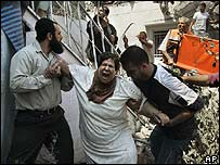 An injured Palestinian woman is helped from a building in Gaza City (17 May)