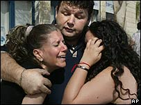 An Israeli man comforts two women after a rocket fired from Gaza lands in Sderot