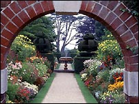 View through the arch showing summer borders and fountain at Nymans Garden
