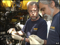 Odyssey co-founder Greg Stemm, left, and project manager Tom Dettweiler examining a coin