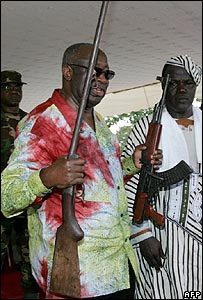 President Laurent Gbagbo holds two weapons at a disarmament ceremony in Ivory Coast
