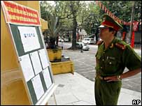 Policeman looks at voting list in Hanoi