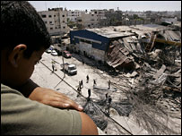A Palestinian boy looks at the rubble of a metal workshop in Gaza destroyed in a missile strike on Saturday 19 May