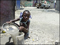 Una niña lava un plato en Cité Soleil, la villa miseria más grande de Puerto Príncipe