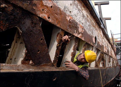 A workman at the stripped down hull of the Cutty Sark