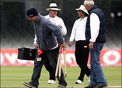 Umpires Rudi Koertzen and Asad Rauf (centre) call a halt to proceedings while the groundstaff remove the wickets