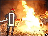 Bombero frente a auto incendiado