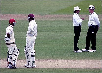 Umpires Asad Rauf and Rudi Koertzen (right) discuss the conditions while West Indies openers Daren Ganga and Chris Gayle (left) look on