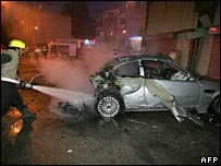 Israeli firefighters douse fire from a car following a rocket attack in Sderot