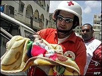 Un miembro de la Cruz Roja Libanesa traslada a una niña de un mes de nacida, evacuada del campamento.