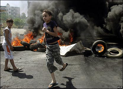 A boy runs in front of burning tyres at the entrance to the Bedawi refugee camp, adjacent to Nahr al-Bared camp