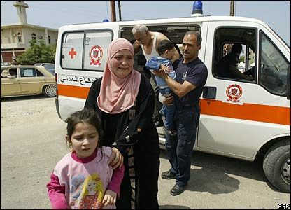 Lebanese civil defence workers evacuate a family from inside the camp