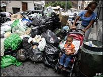 Resident pushes stroller past pile of rubbish in Naples
