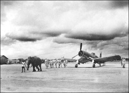 An elephant pulls an aircraft into position on a Fleet Air Arm airfield in India.