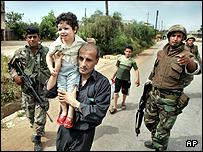 A man carries a child past Lebanese soldiers as they flee Nahr al-Bared refugee camp, Lebanon.