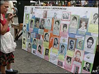 Woman looks at photos of El Salvador's civil war dead in San Salvador