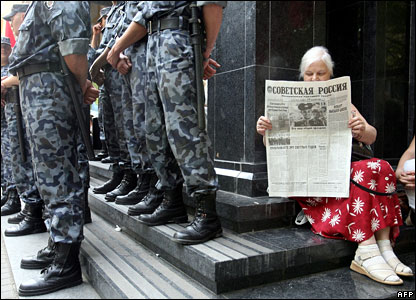 A Ukrainian woman reads a newspaper near the entrance of the General Prosecutor's office in Kiev, which is being guarded by special police