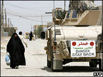 An Iraqi woman passes a US marines' vehicle in Falluja, Iraq