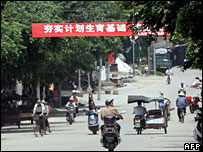 A bright red-and-white banner bearing the slogan 'support the one-child policy' hangs across the road leading to Bobai